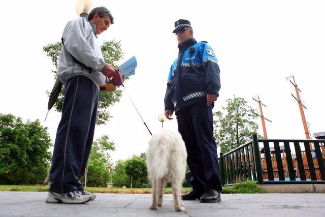 Policía local con el dueño de un perro
