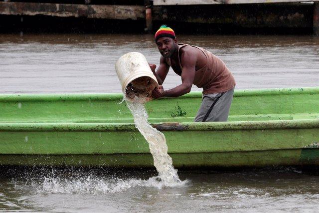 Un hombre achica agua de una barca ante la llegada del huracán 'Otto'