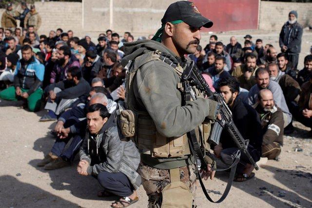 Un soldado comprueba identidades de hombres en Mosul