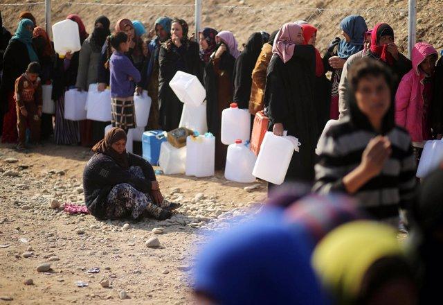 Desplazados en Mosul con garrafas de agua