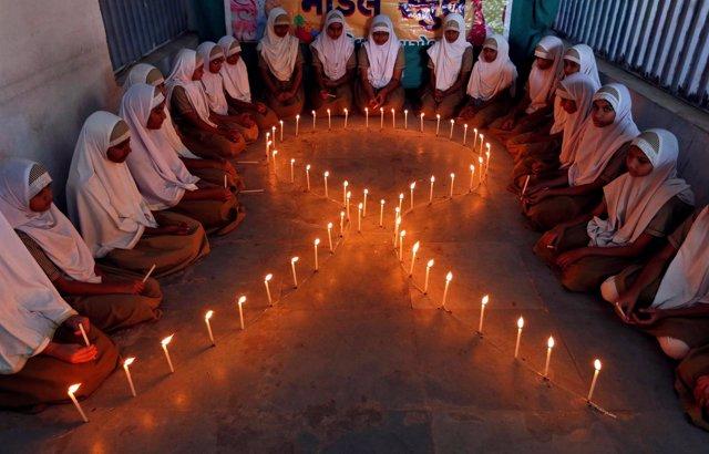 Niñas junto a velas con forma de lazo en el Día Mundial del Sida