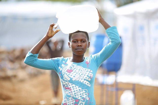 Una adolescente carga agua en el campo de refugiados de Mahama, Ruanda
