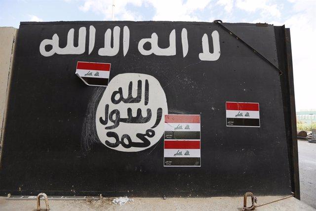 Muro pintado con la bandera de Estado Islámico en Tikrit (Irak)