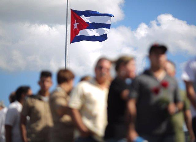 Bandera de Cuba mientras ciudadanos se despiden de Fidel