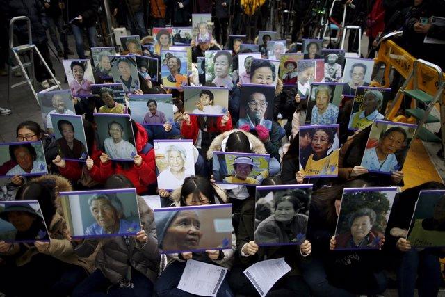 """Manifestantes sujetan los retratros de """"mujeres para confort""""  fallecidas"""