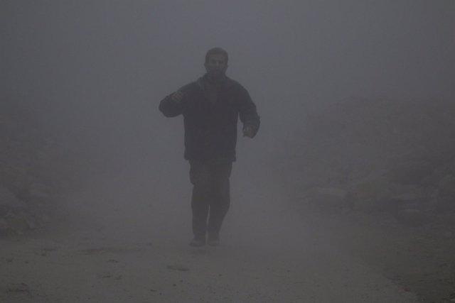 Un hombre camina entre el polvo tras un ataque en la zona rebelde de Alepo