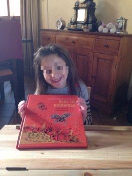 La niña Nadia Nerea posa con el libro 'Alas de mariposa'