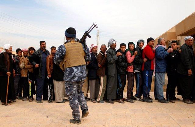Un grupo de residentes de Mosul hace fila para recibir las ayudas de la ONU.