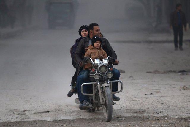 Una familia abandona la zona rebelde de Alepo