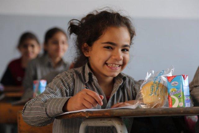 Una niña en el colegio con una de las comidas escolares del PMA