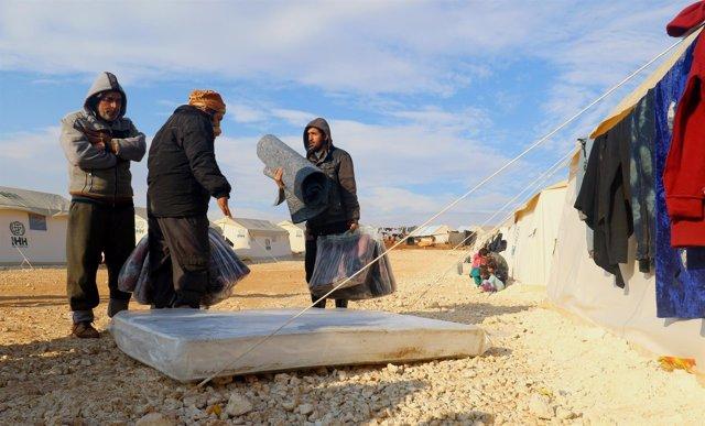 Varios desplazados desde Alepo reciben colchones al llegar a un campo de Idlib.