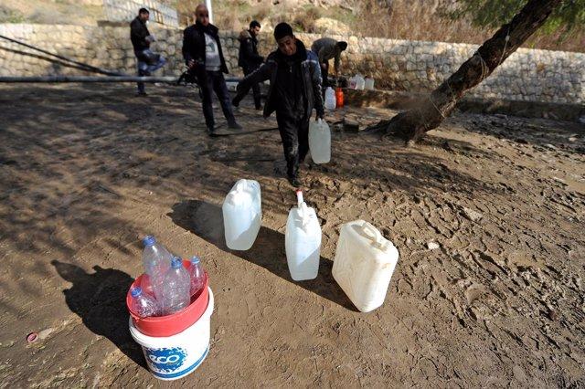 Personas recogen agua en Damasco