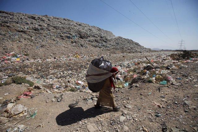 Una niña recoge basura a las afueras de Saná