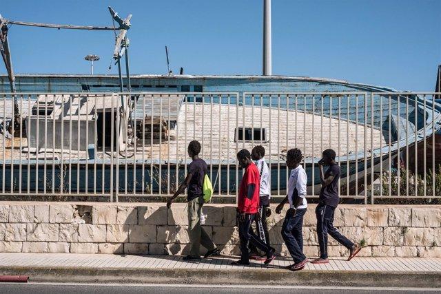 Menores gambianos frente a un cementerio de barcos en Libia
