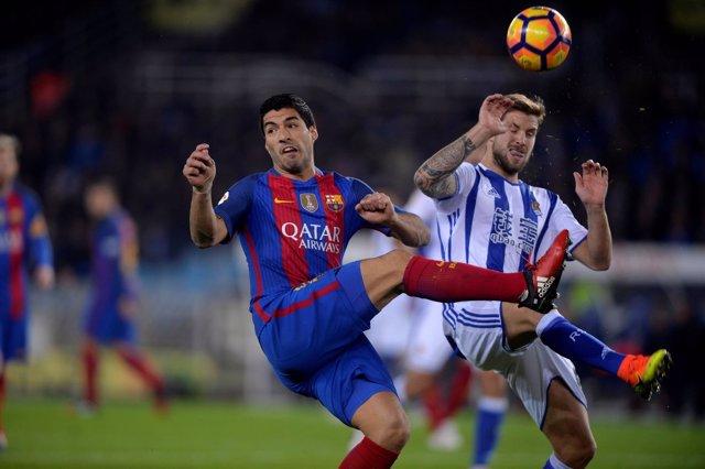 Luis Suárez e Íñigo Martínez pelean un balón en Anoeta