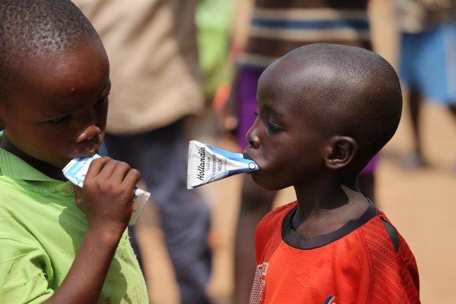 Dos niños toman leche evaporada en un campo de desplazados de Nigeria.