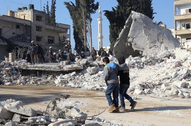 Niños caminan junto a escombros tras un bombardeo en Idlib