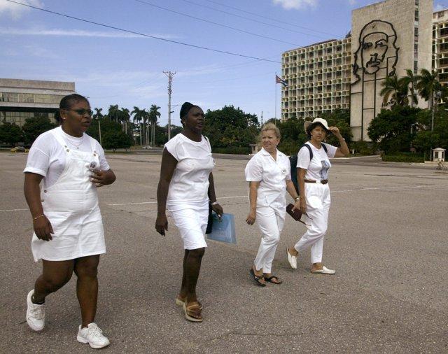 Lidice Moya, Berta Soler, Marcela Sanchez and Dolia Leal (L-R) walk underneath t