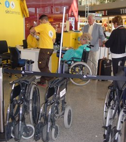 Personal Atiende A Una Persona En El Punto De Movilidad Reducida Del Aeropuerto