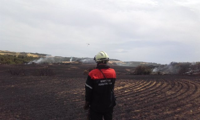 Un bombero afecta un campo quemado en Navarra