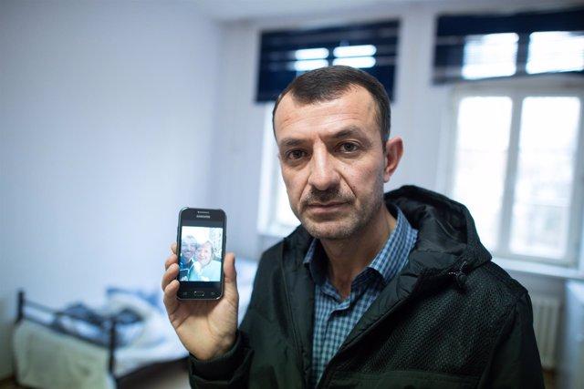 Un solicitante de asilo en Alemania muestra su móvil con una foto con Merkel