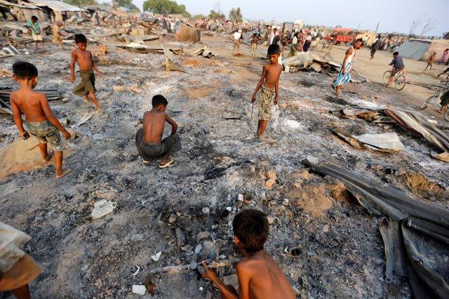 Niños buscando entre sus viviendas quemadas en Rajine, Birmania