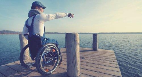 Un joven en silla de ruedas señala el horizonte