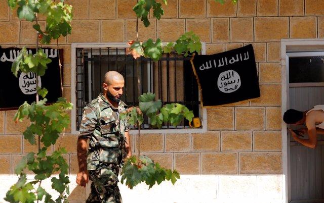 Miliciano del Ejército Libre Sirio en Jarablus ante banderas del Estado Islámico