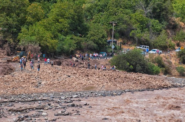 People walk along a damage road after a flood near Santiago, Chile February 26,