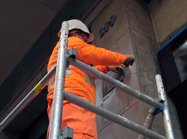 Retirada de una placa franquista con yugo y flechas en una finca de Barcelona