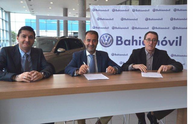 En el centro el director gerente de Bahíamovil, Jesús Rivas., firma el acuerdo.