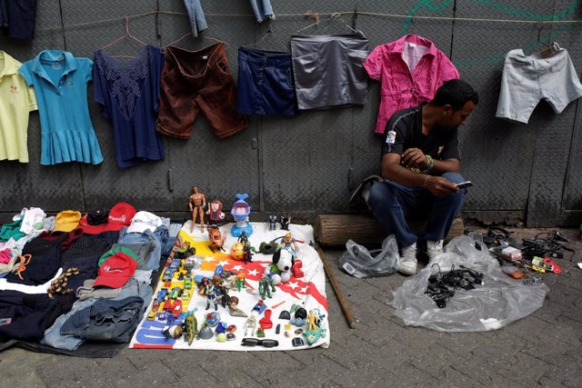 A vendor sits next to second-hand toys and clothes at a street market in the slu