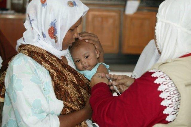 Mujer y niño recibe una vacuna