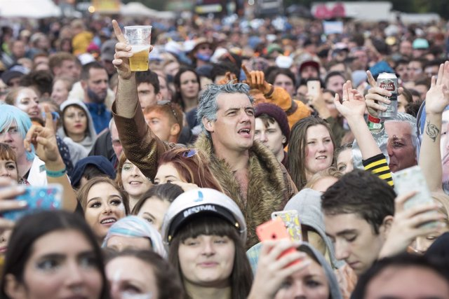 Festival goer holds a pint up in the mainstage crowd on day 3 of Bestival 2016,