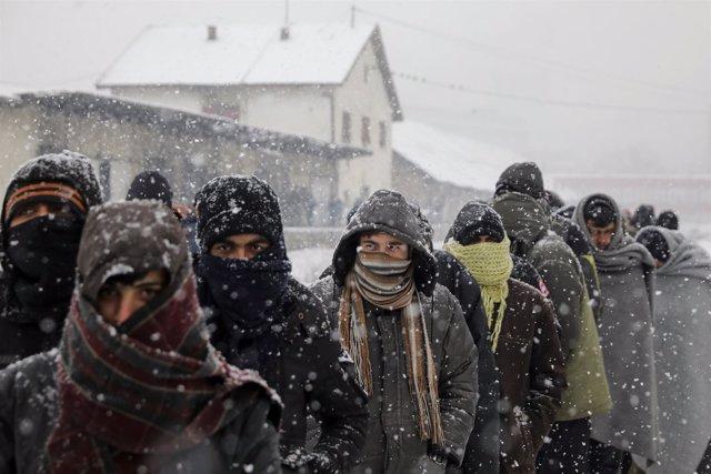 Refugiados hacen cola bajo la nieve para comer