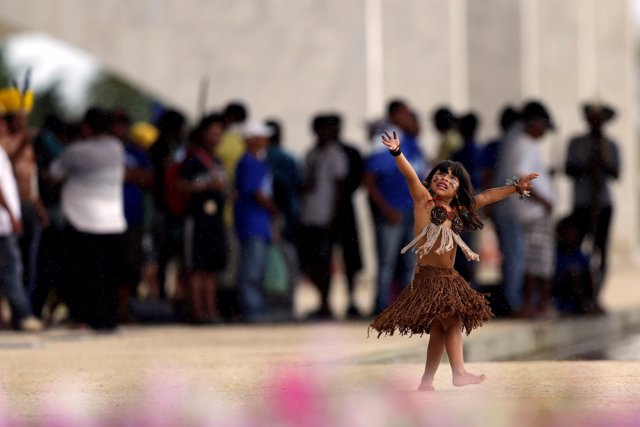 Indigenous children from the Kaingang ethnic group are seen dancing during a pro