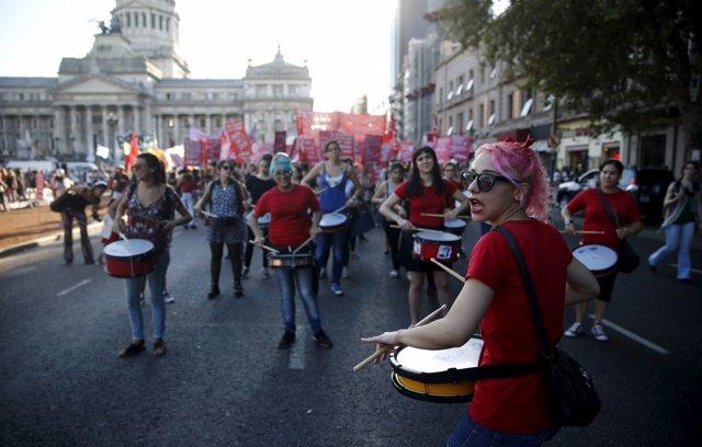 A woman beats a drum during a demonstration to mark International Women's Day an