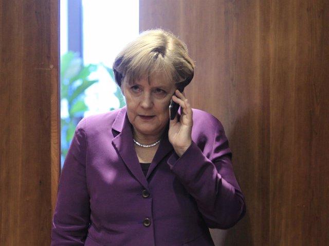 Angela Merkel habla por su teléfono móvil, celular