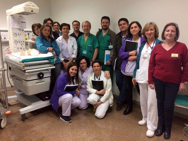 Once monitores de simulación clínica posan junto a un robot bebé en La Fe