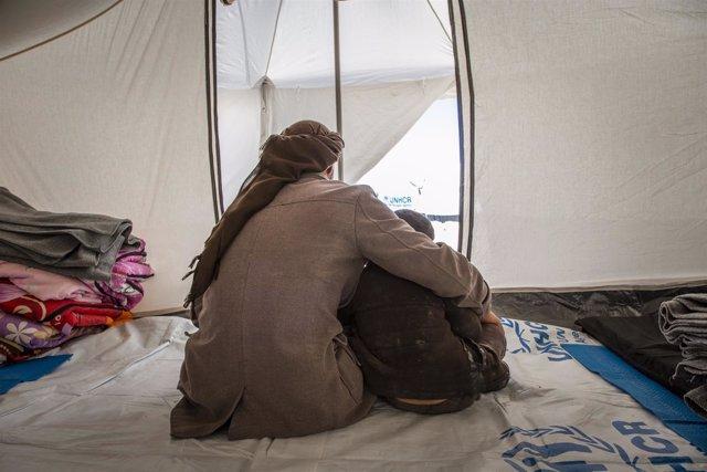 Un padre con su hijo en un campo de desplazados en Siria