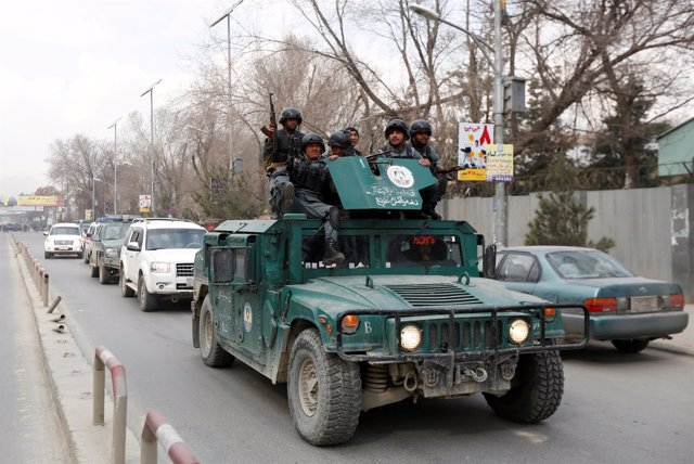Afghan policeman arrive at the site of a blast and gunfire in Kabul, Afghanistan