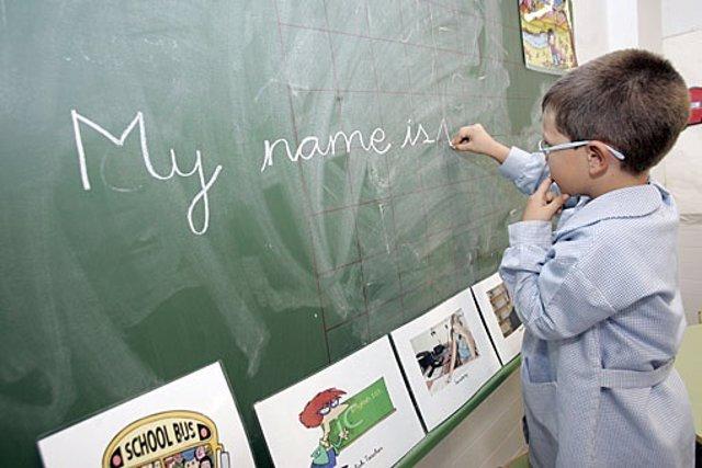 Imagen de archivo de un niño que escribe inglés en la pizarra del colegio