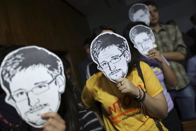 Personas utilizando máscaras con el rostro de Edward Snowden.