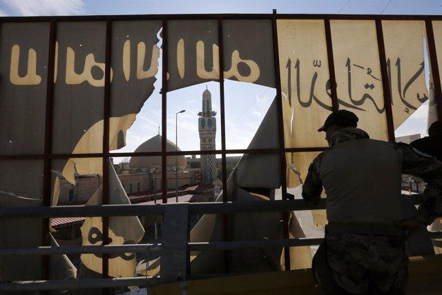 Militar iraquí junto a logo de Estado Islámico