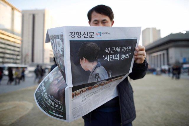 Un surcoreano lee un periódico que muestra el impeachment de Park