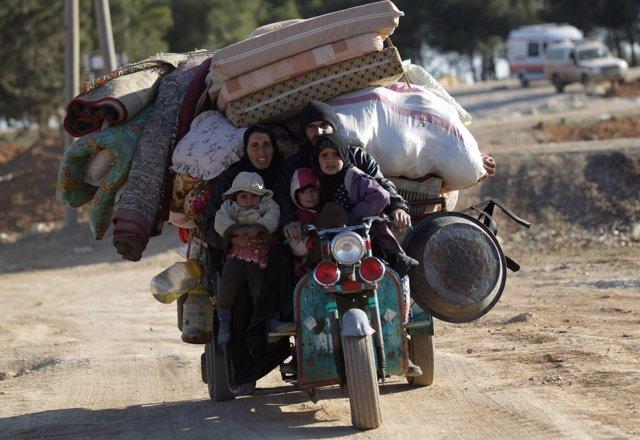 Familia siria huye con todas sus pertenencias de Al Bab