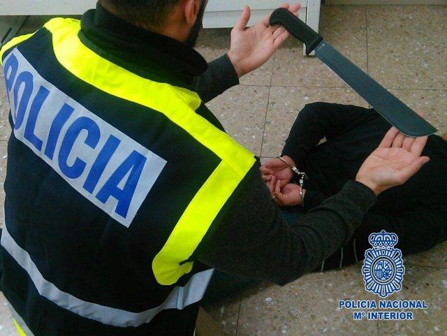 Agente con uno de los detenidos y el machete utilizado