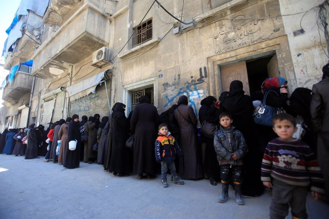 Mujeres y niños sirios hacen cola para recibir ayuda en Alepo.