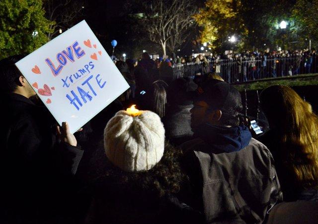 """Un manifestante con una pancarta que dice """"el amor triunfa sobre el odio"""""""