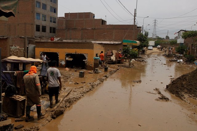 People walk after a landslide and flood in Lurigancho district in Chosica, Peru